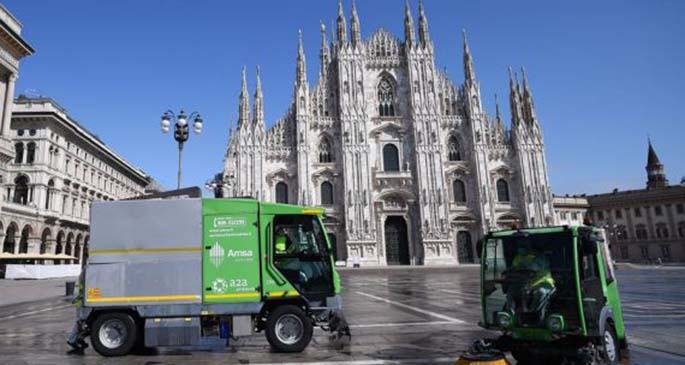 Sanitation workers clean the ground at Piazza del Duomo in Milan, Italy, on March 31, 2020.(Photo by Daniele Mascolo/Xinhua)