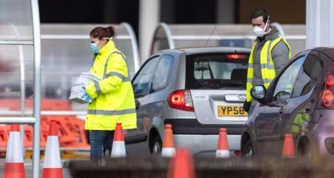 Staff carry equipments at a drive-through COVID-19 test station set up in the parking lot of an IKEA store in Wembley, northwest London, Britain, March 31, 2020.(Photo by Ray Tang/Xinhua)