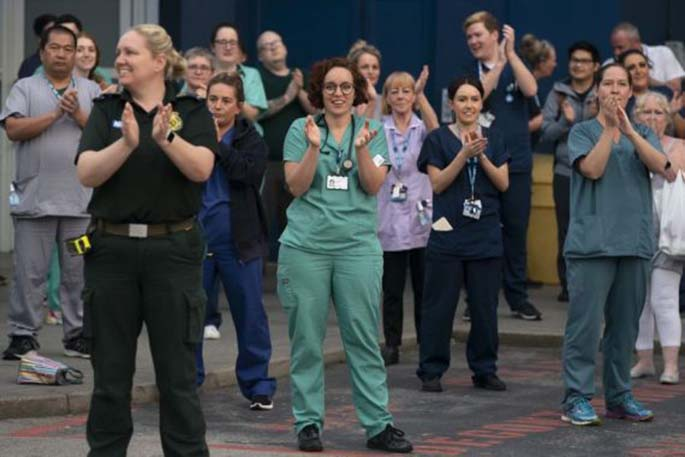 "National Health Service (NHS) staff members applaud outside the Royal Liverpool University Hospital during the weekly ""Clap for Our Carers"" campaign in Liverpool, Britain, April 23, 2020. (Photo by Jon Super/Xinhua)"