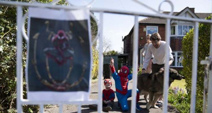 Children wait for Jason Baird, who runs a martial arts academy in South Manchester, dressed up as Spider-Man to entertain the public amid the COVID-19 outbreak in Manchester, Britain on April 13, 2020. (Photo by Jon Super/Xinhua)