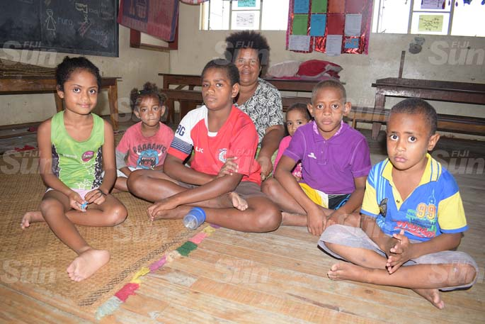 Keyasi Siva 47 (sitting at the back) with Children from Wainividio Settlment in Navua (from left) Makitalena MManiova, Nanise Marama, Jonetani Kovelali, David Carl, Elizabeth Sivowale and Inia Bola were part of the twelve familes that took shelter at Vashist Muni Memorial Primary School.  These twelve familes had their house flooded on Tuesday night and were adviced by Police to move to Evecuation centre . The thirty three member twelve familes were placed in six to eight people in one room oly as Police wanted them to practice social distancing at the same time.  Photo: Ronald Kumar.