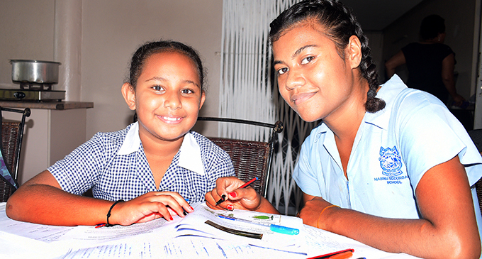 Elizabeth Qaqaturaga 10, a year 5 students at CMF primary school and with her cousin sister, Meresaini Serau 18, a year 13 student at Nasinu Secondary School doing home study in their school uniform and following school timetable at home on April 22, 2020. Photo: Ronald Kumar.