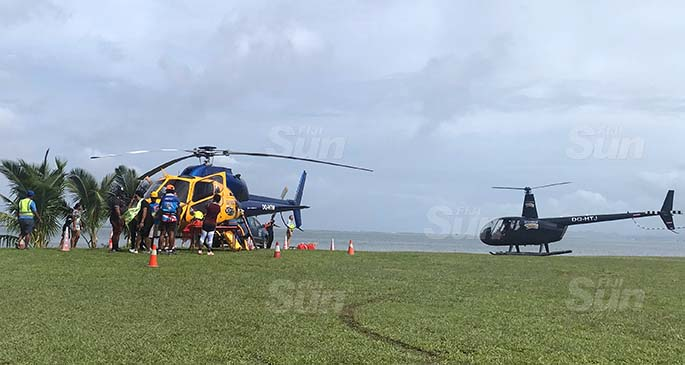 The LifeFlight Fiji team standing infront of the AS355 twin squirrel engine helicopter (left) while the The Robinson R44 comes in after taking a group on a 15 minutes scenic tour of Suva on June 6, 2020. Photo: Maraia Vula