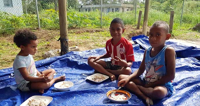 Children of Korociri in Nadi tuck into their meals.