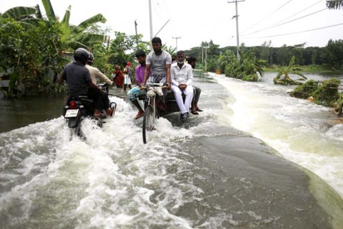 People make their way through a flooded road in Munshiganj on the outskirts of Dhaka, capital of Bangladesh, on July 27, 2020. (Xinhua)