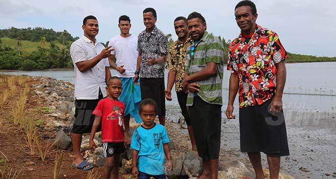 Youths of Viro Village at the new village's seawall. Photo: Kelera Sovasiga