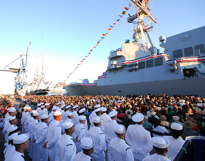 """Crew members of the guided-missile destroyer USS Sterett (DDG 104) await the command to """"board the ship and bring her to life"""" during the ship's commissioning ceremony at the South Locust Point Marine Terminal in Baltimore."""