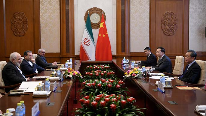 China's Foreign Minister Wang Yi talks to Iran's Foreign Minister Mohammad Javad Zarif during a meeting at the Diaoyutai state guest house on December 31, 2019 in Beijing, China.