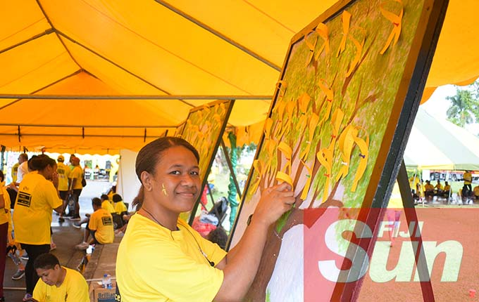 Sasenieli Tabua put up her yellow ribbon support message of yellow ribbon tree during Fiji Corrections Service annual yellow ribbon walk at Albert park on October 31, 2020. Photo: Ronald Kumar.
