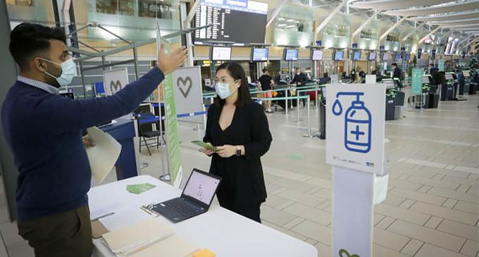A woman listens to instructions on a pilot project of rapid COVID-19 testing before taking flights at Vancouver International Airport in Richmond, British Columbia, Canada, on Nov. 30, 2020. (Photo by Liang Sen/Xinhua)