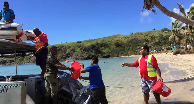 Red Cross teams move needful supplies to families in disaster zones using maritime support.