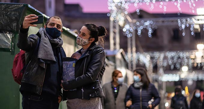 People wearing face masks take selfies at the Fair of Santa Llucia in Barcelona, Spain, on Dec. 1, 2020. The Fair of Santa Llucia is held in Barcelona from Nov. 27 to Dec. 23 with capacity restricted to 30% amid the COVID-19 pandemic. (Photo by Joan Gosa/Xinhua)