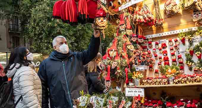 People wearing face masks look at Christmas decorations at the Fair of Santa Llucia in Barcelona, Spain, on Dec. 1, 2020. (Photo by Joan Gosa/Xinhua)