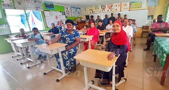 Parents, teachers and donors with the new school desks inside the Year 8 classroom at Rahmatullah Khan Memorial School. Photo: Mereleki Nai