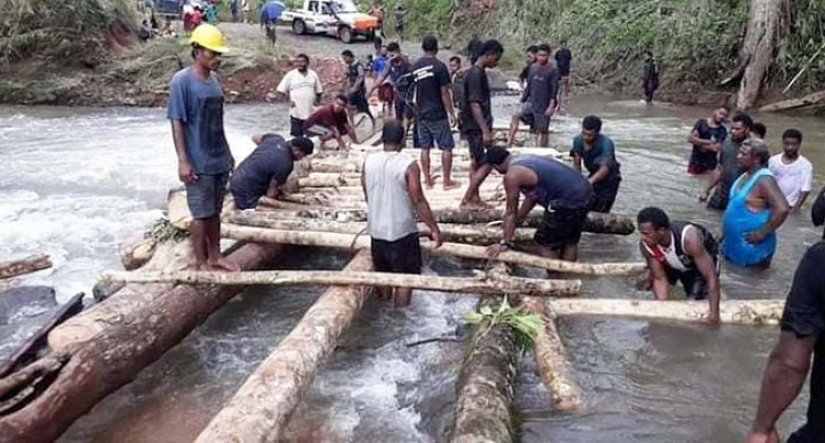 Youth, Villagers Build Tree Trunk Bridge