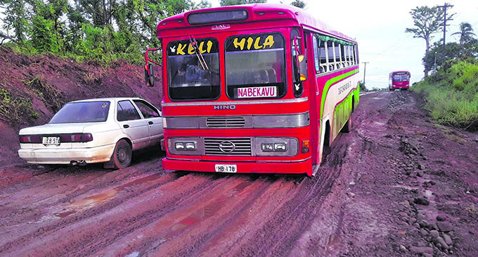 A Dalip Chand and Son Buses Limited and a vehicle bogged on a road in the North.  Photo: Dalip Chand and Son Buses Limited