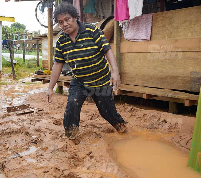 Titilia Saluvanua 51 walks through mud brought with flash flooding in their home and compound at Davuilevu, Nausori on March 9, 2021. Photo: Ronald Kumar