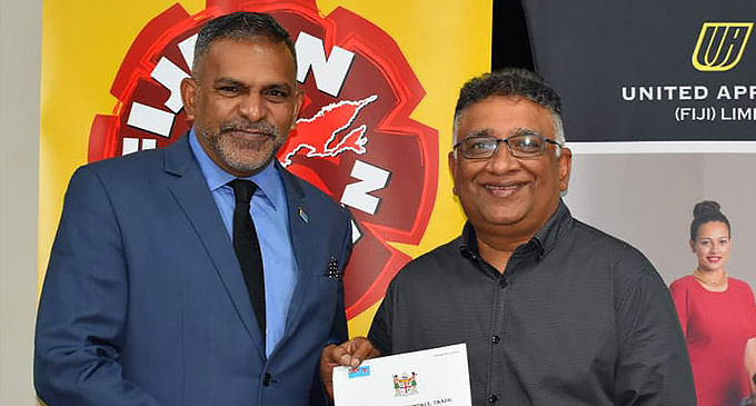 Minister for Commerce Faiyaz Koya hands over a Fijian Sewn licence to United Apparel Limited General Manager Mahesh Patel on March 30, 2021, in Suva.