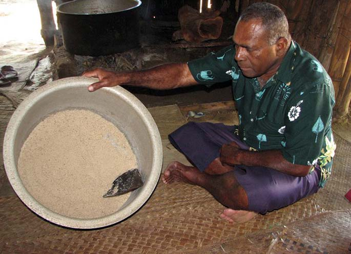 A Lomawai villager showing the salt that was traditionally collected in the pot.